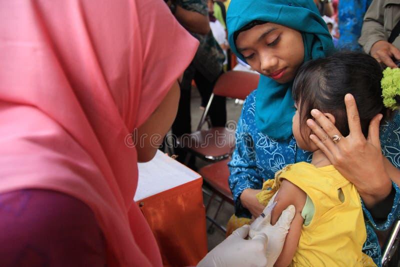苏拉巴亚印度尼西亚,可以21日2014年 公共卫生工作者给了接种孩子 免版税库存图片