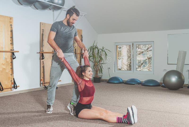 英俊的与帮助年轻健身女孩的胡子的瑜伽男性个人教练员在坚硬训练锻炼以后舒展她的肌肉,稀土 免版税库存照片
