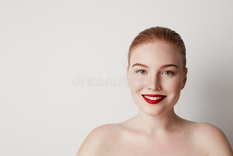 英俊的与摆在白色背景的轻的裸体构成的红头发人女性模型 库存图片