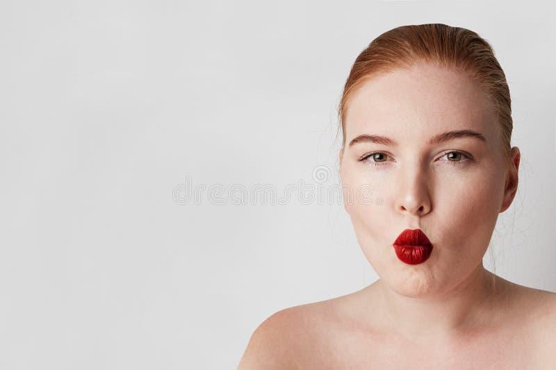 英俊的与摆在白色背景的轻的裸体构成的红头发人女性模型 免版税库存照片