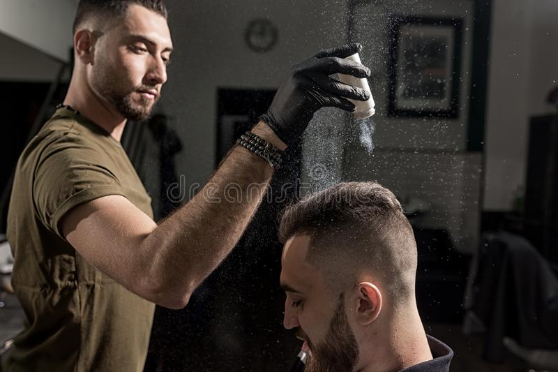 英俊的理发师在理发店固定称呼有一干燥styler的残酷年轻人 库存图片
