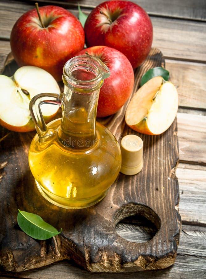 苹果汁醋用在一个切板的新鲜的红色苹果 免版税库存照片