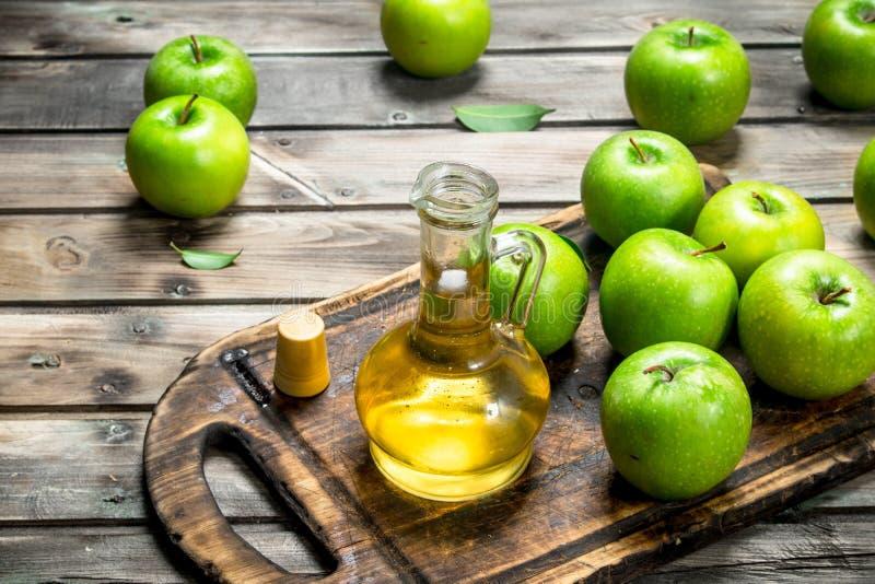 苹果汁醋用在一个老委员会的绿色苹果 免版税图库摄影