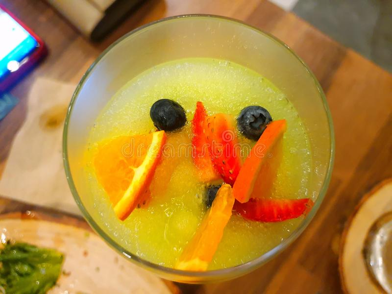 苹果鸡尾酒顶视图用桔子、草莓切片和蓝莓在玻璃 图库摄影