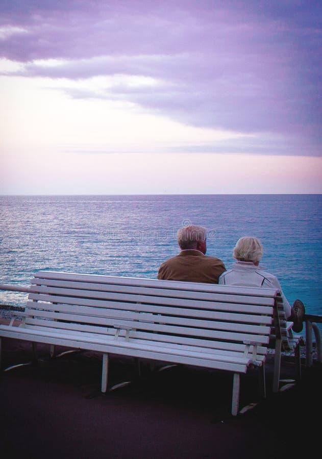 老夫妇坐看风平浪静的长凳 库存照片