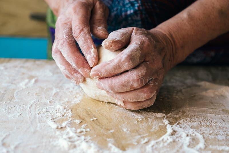 老妇人揉的面团的起皱纹的手 图库摄影