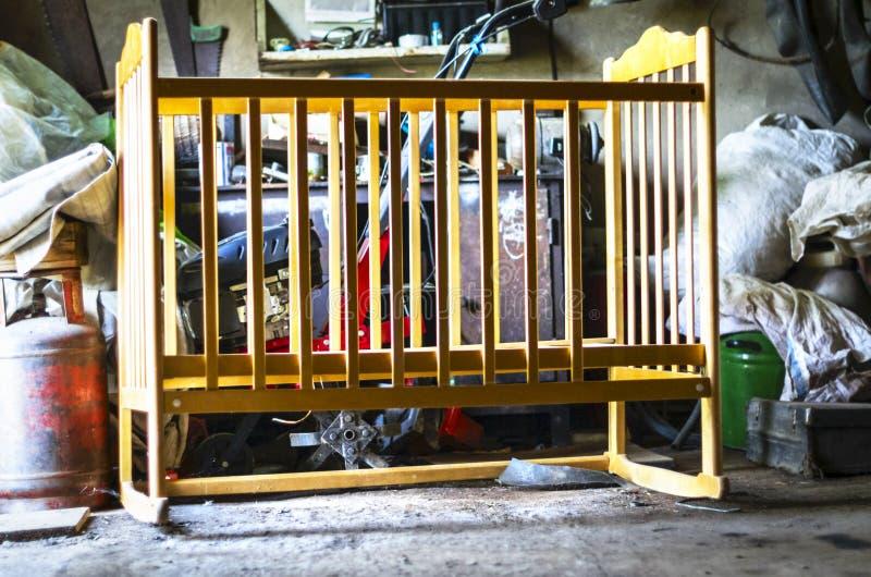 老木婴孩小儿床,摇篮,轻便小床床在一个杂乱存贮棚子,车库 长大,生活路线概念 免版税库存图片