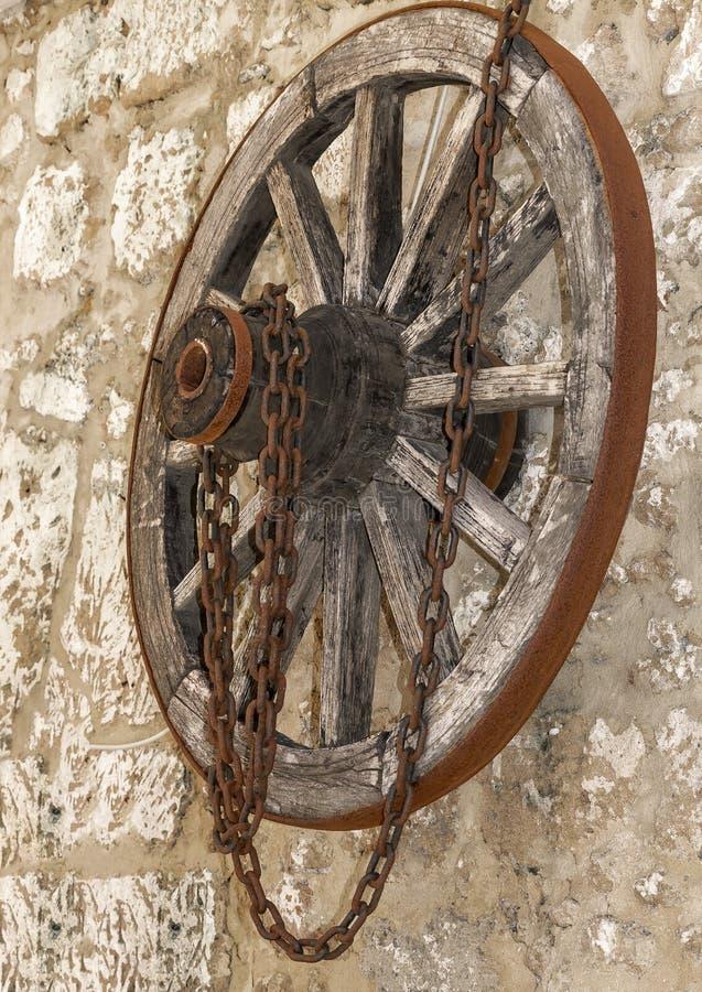 老有垂悬在石房子墙壁上的生锈的金属链子的葡萄酒木轮子 侧视图 图库摄影
