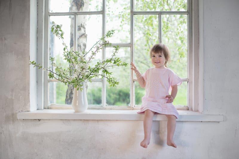 老窗台的美丽的小女孩与春天开花 库存照片