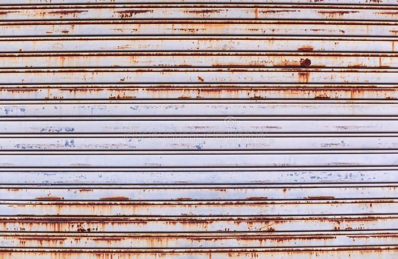 老详细的年迈的葡萄酒生锈的织地不很细锌合金金属路辗快门门,用于建筑的商店前面外部设计 图库摄影