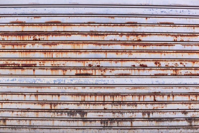 老详细的年迈的葡萄酒生锈的织地不很细锌合金金属路辗快门门,用于建筑的商店前面外部设计 免版税库存图片