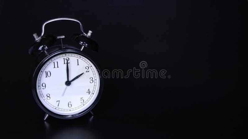 老黑葡萄酒闹钟的接近的图象 两个o `时钟 库存照片