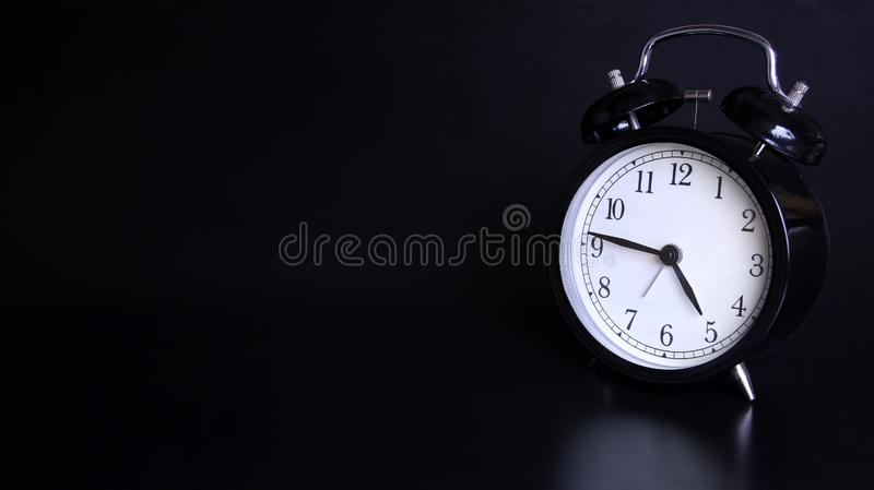 老黑葡萄酒闹钟的接近的图象 4点和四十五分钟 库存照片