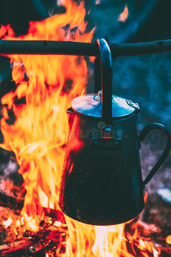 老铁阵营水壶在黄昏晚上煮沸在火的水在森林明亮的火焰火篝火 免版税图库摄影