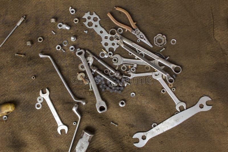 老金属工具和螺丝坚果在一个肮脏的粗麻布特写镜头 毛面纹理 库存图片