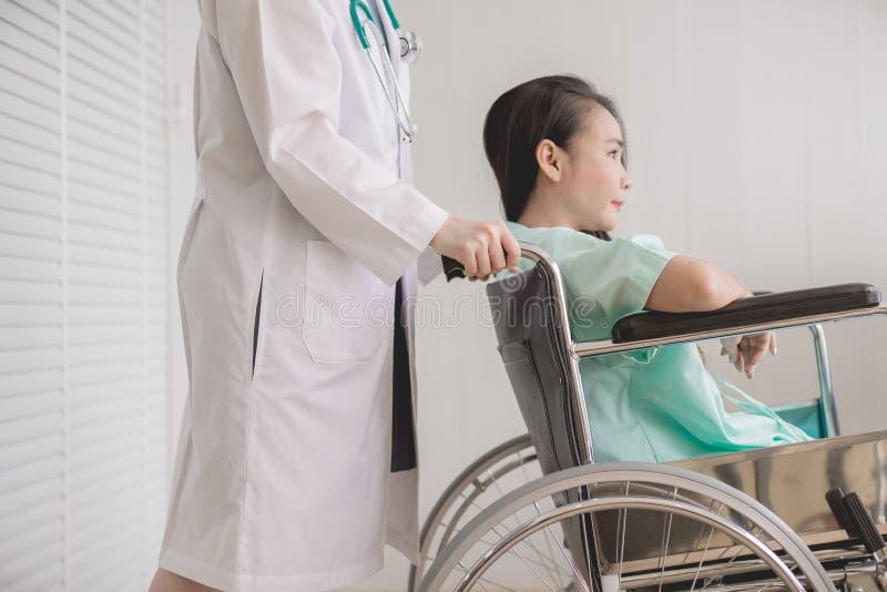 耐心亚洲妇女麻痹在有站立在拖拉对她,医疗保健概念后的医生的一个轮椅坐 免版税库存照片