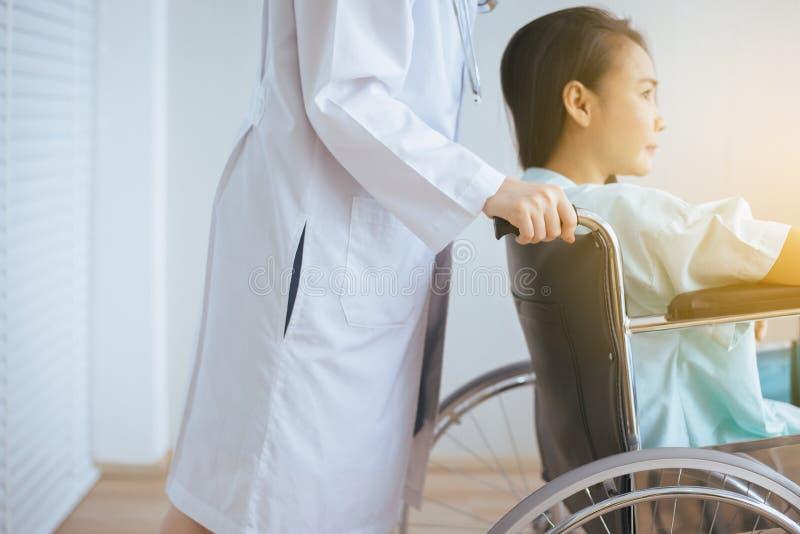 耐心亚洲妇女麻痹在有站立在拖拉对她,医疗保健概念后的医生的一个轮椅坐 库存照片
