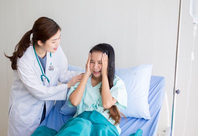 耐心亚裔妇女有严重的头疼或的偏头痛在医院 免版税图库摄影