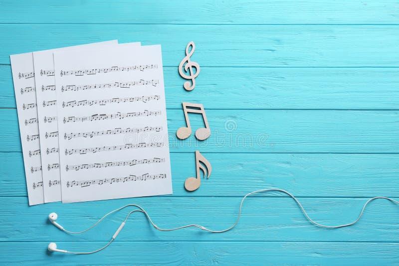 耳机、音乐笔记和板料在木背景,平的位置 免版税库存图片