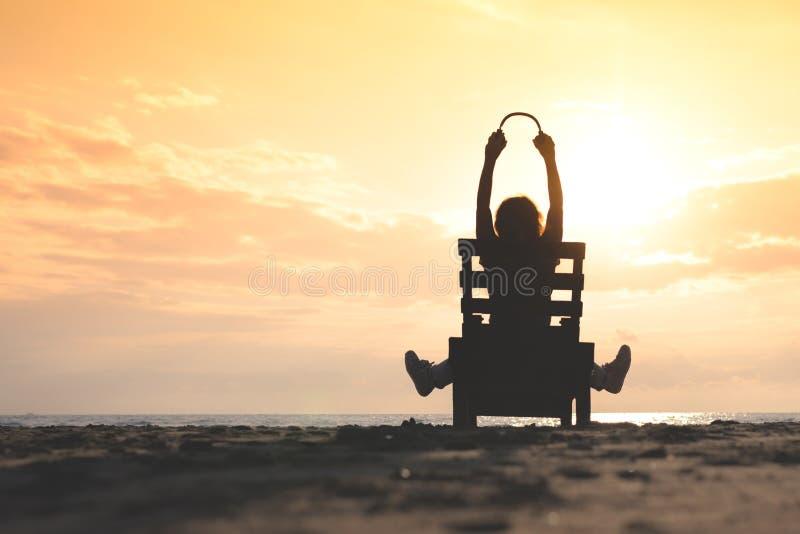 耳机的女孩坐听到在海滩的音乐的太阳懒人在日落 免版税库存图片