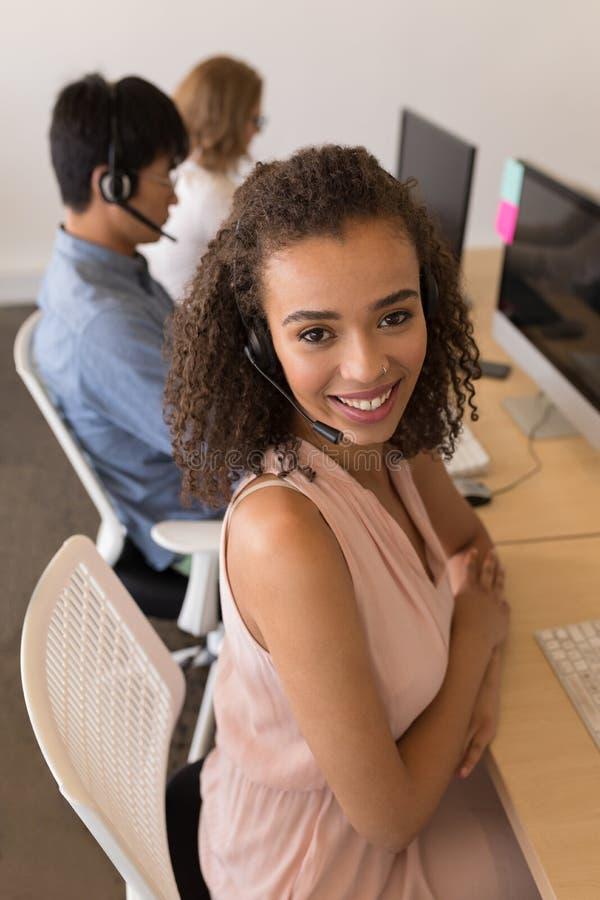 耳机的女性执行委员微笑在办公室的 免版税库存图片