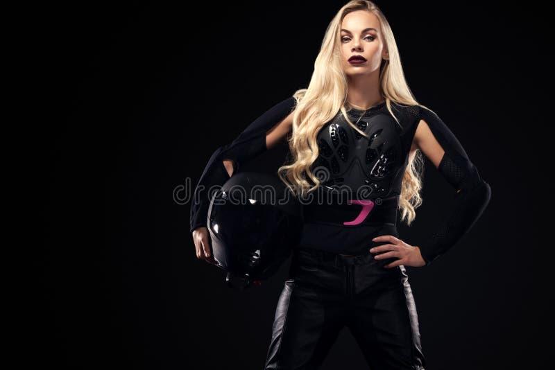 耳机的时装模特儿DJ和骑自行车的人,黑皮夹克,皮革裤子,时髦的俏丽的白肤金发的妇女在夜 免版税库存图片