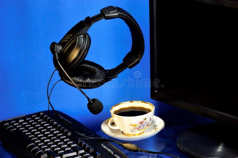 耳机计算机耳机、话筒、显示器、键盘和一杯咖啡活泼的 网络商店的计算机耳机, 库存照片