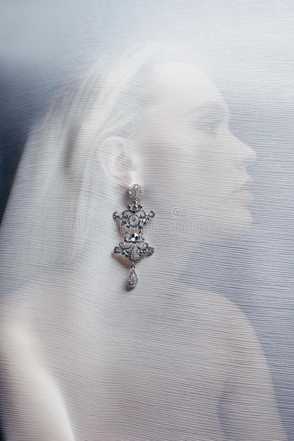 耳环和首饰在一名性感的妇女的耳朵插入一种透明织品 完善的白肤金发的女孩,华美神奇 免版税图库摄影