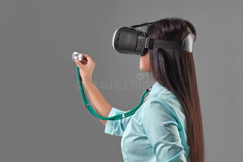 虚拟现实玻璃的年轻可爱的医生 库存照片