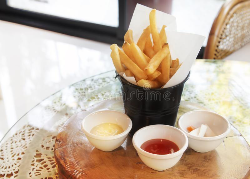 薯条在一个木盘子被安置 用西红柿酱和乳脂状的牛奶 在餐馆桌上 中心焦点 图库摄影