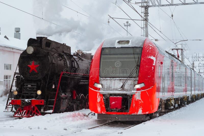 蒸汽机车和现代多单元火车立场附近在驻地 免版税库存图片