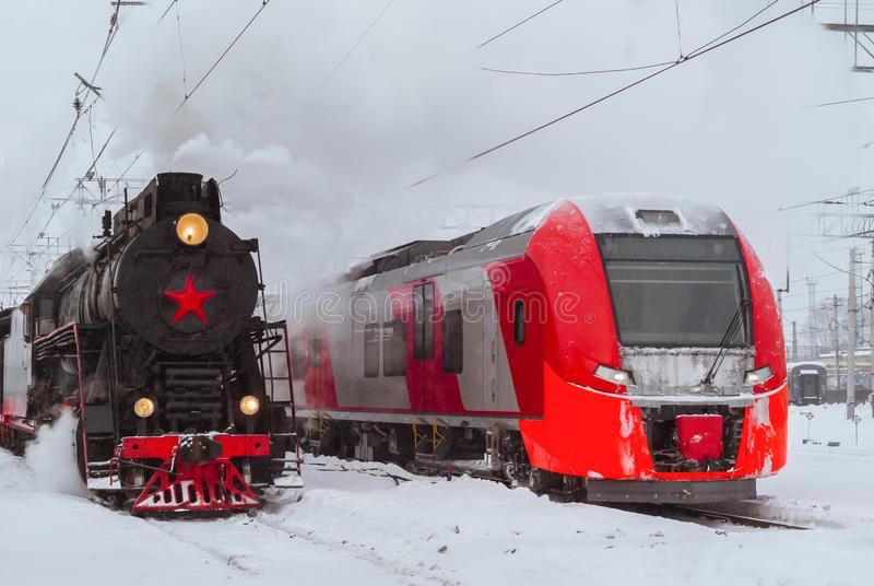 蒸汽机车和现代多单元火车立场附近在驻地 免版税库存照片