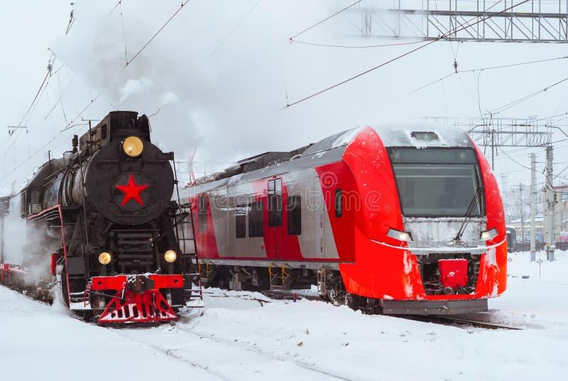 蒸汽机车和现代多单元火车立场附近在驻地 图库摄影