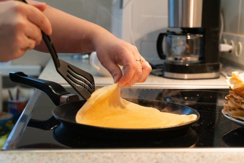 薄煎饼在平底锅油煎 烹调在一个电火炉的薄煎饼的过程 免版税库存图片