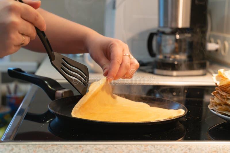 薄煎饼在平底锅油煎 烹调在一个电火炉的薄煎饼的过程 库存照片