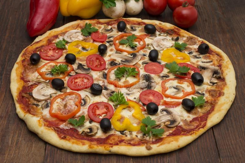薄饼用火腿、胡椒和橄榄 在木背景的可口意大利薄饼 免版税图库摄影