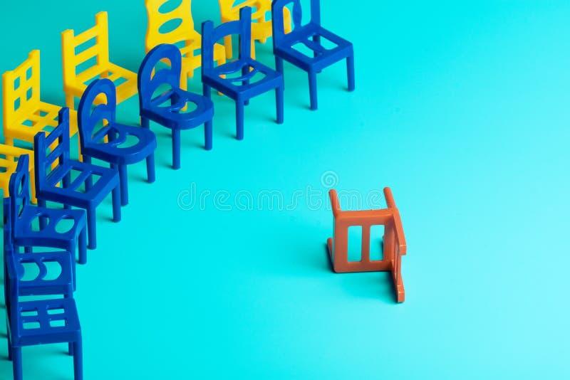 È caduto la sedia rossa che è stato vicino lui in un semicerchio, due file delle sedie nei colori differenti, sedie di plastica immagini stock libere da diritti