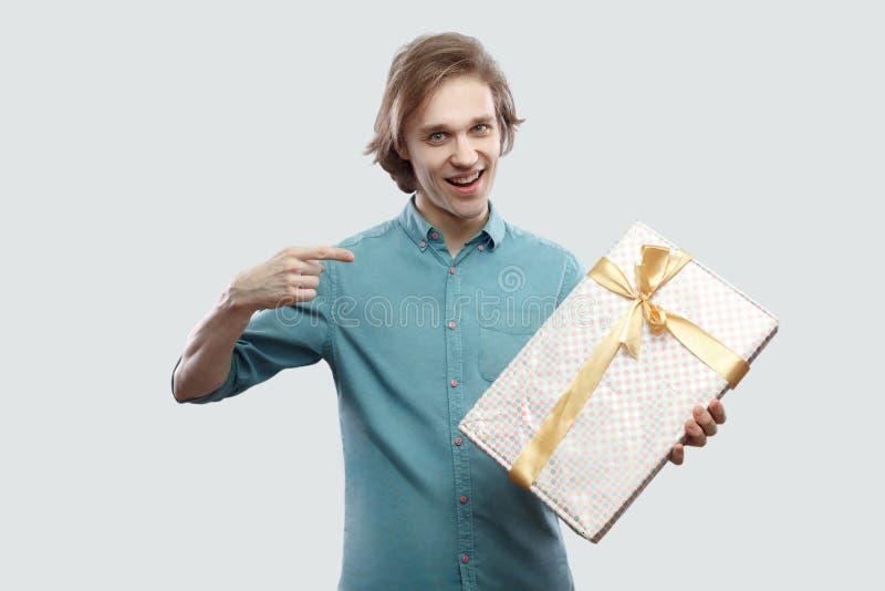 È il vostro! Giovane moderno soddisfatto in condizione blu-chiaro della camicia e dito indicare per presentare con l'arco giallo  immagine stock
