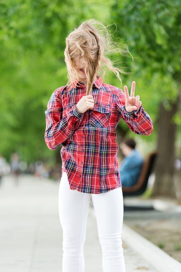 ? ventoso fuori Piccolo bambino con capelli sudici il giorno di estate Il bambino sveglio gode dei suoi capelli che ondeggiano e  fotografie stock libere da diritti