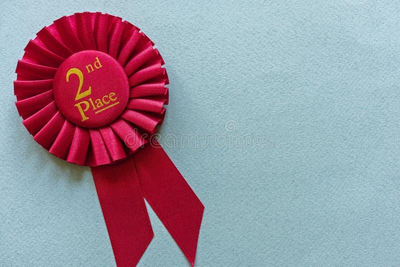 2ème rosette de gagnants d'endroit de rouge sur bleu-clair images stock