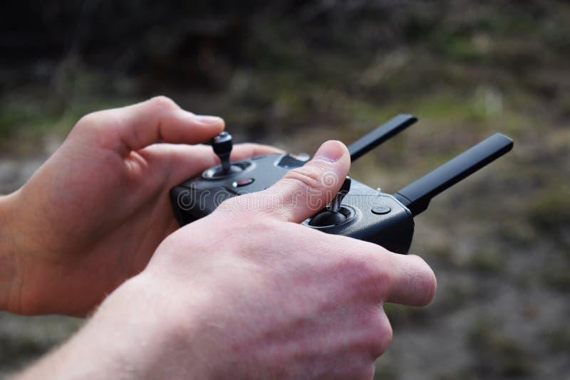 遥控为quadrocopter,特写镜头 控制移动的设备的发射机在男性手上 电子,爱好, 图库摄影