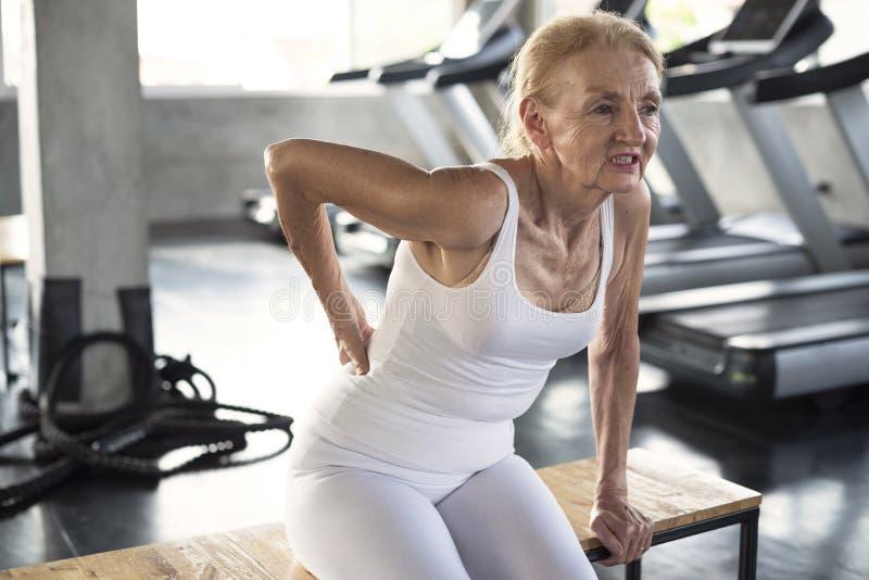 遭受健身的腰疼原因的资深妇女伤害 免版税库存照片