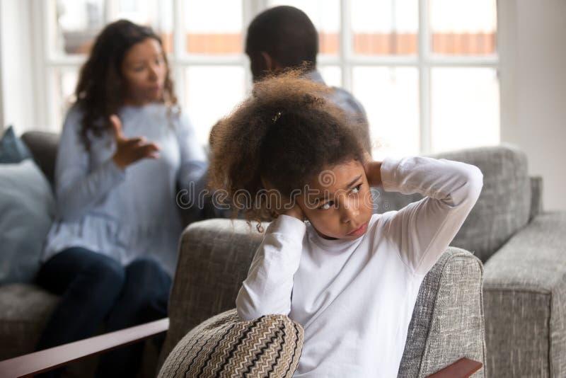 避免家庭冲突的生气小黑女孩盖子耳朵 免版税库存照片
