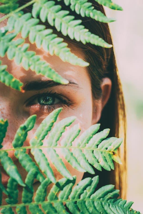 面对的一片年轻愉快的秀丽红色头发女孩妇女藏品蕨叶子的画象在夏天公园森林里 免版税库存照片