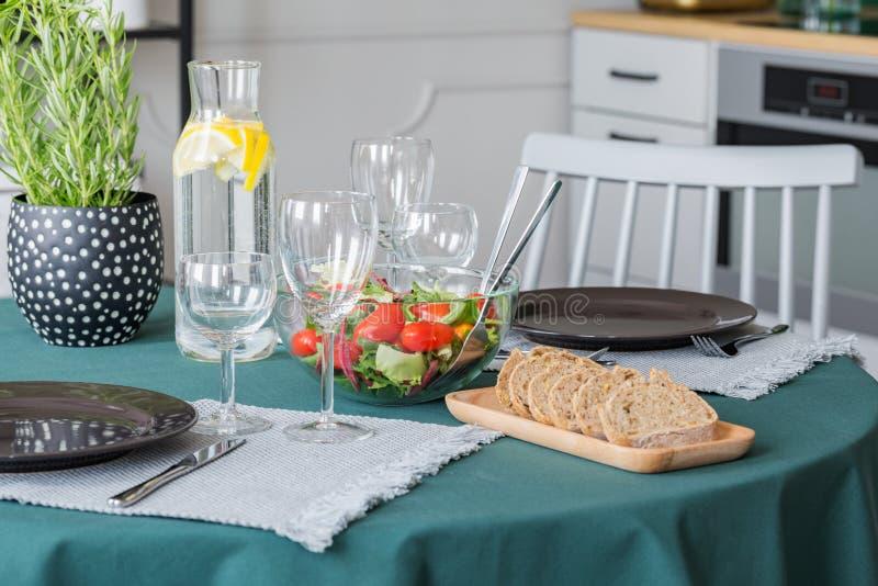 面包、沙拉、板材和酒杯在用鲜绿色桌布盖的桌上 库存照片