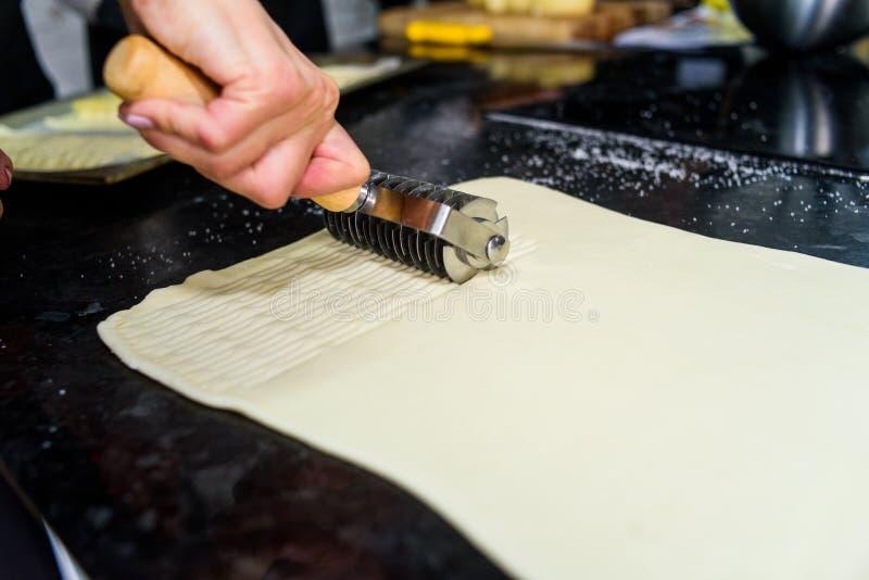 面团在桌上的切口过程通过使用特定工具 库存照片