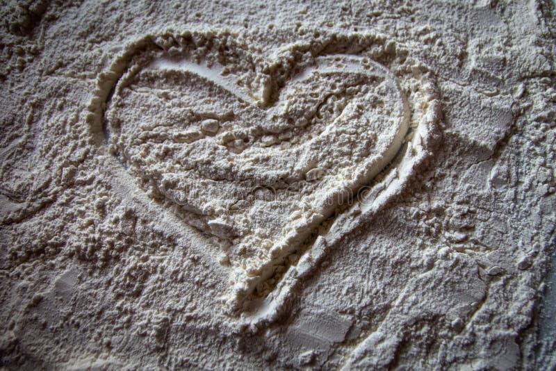 面粉的心脏在一块白色板材的 免版税库存照片