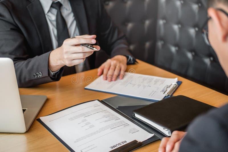 面试概念,读简历的高级管理人员在面试雇员年轻人会议申请人期间和 库存照片