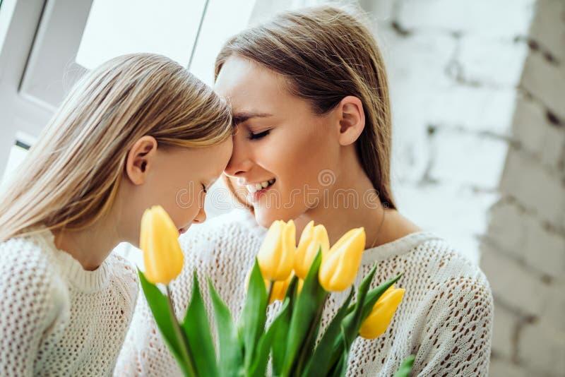 非常爱 美丽的母亲和年轻女儿在家坐窗台 免版税库存照片