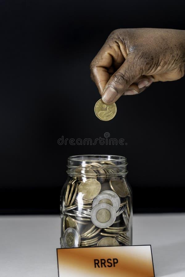 非裔美国人的尼日利亚妇女落下的硬币到RRSP瓶子里 库存图片
